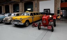 A Checker Aerobus stands next to a Porsche tractor in the Meilenwerk Berlin. (Photo by Ronan McGrath.)
